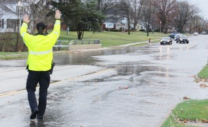 Photo by RR Best A Sullivan police officer waves traffic back away from the Asa Creek bridge in Sullivan Sunday after heavy downpours caused flash flooding.