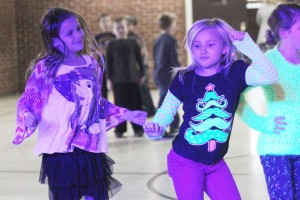 Photo by Keith Stewart OVES third graders Abby Luckenbill (left) and Lexie Bartimus (right) enjoy the fruits of their labor during a school dance Friday after they organized a toy and canned food drive at their school last week.