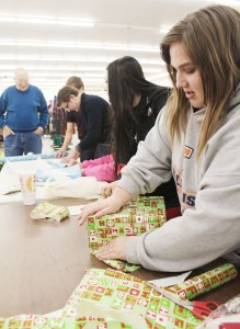 Photo by Keith Stewart Sullivan High Schooler Beretta Phelps puts the finishing touches on the gift wrapping at Shopko last Thursday. She along with other high school students helped wrap gifts as they were purchased through Secret Santa, which this year has seen an increase in the need for assistance.