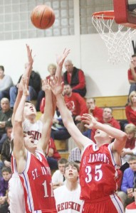 Photo by Keith Stewart Sullivan's Ty Molzen stretches above two St. Anthony defenders for the rebound Tuesday night.