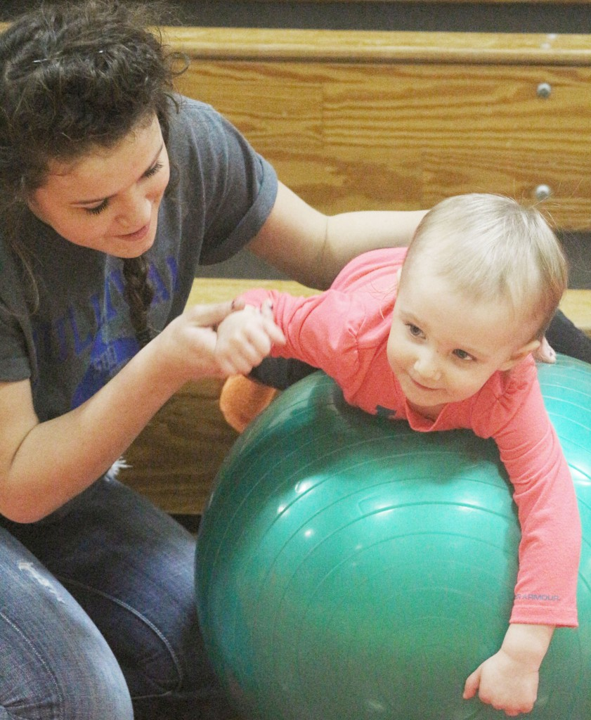 Photo by Keith Stewart SHS student volunteer Cadisen Nuzzo helps Avery Florey balance on an exercise ball last Thursday during the third annual Family Fit Night.