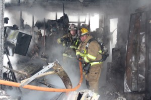 Photo by RR Best Sullivan firefighter Rob Young and Findlay assistant fire chief Jason Fleshner survey the damage inside the home located at 606 West Main Street in Bethany Sunday.