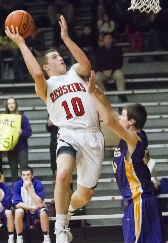 Photo by Keith Stewart Nick Frerichs drives up and over a Monticello defender Wednesday night. The junior not only had 21 points on the night, but also proved crucial in keeping Monticello's Nick Stokowski to just eight points.