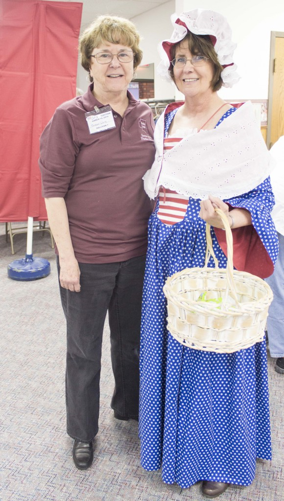 Photo by Keith Stewart Betsy England Moultrie County Clerk Georgia England (right) stands dressed in patriotic wear as Betsy Ross at Faith Lutheran Church in Sullivan during Tuesday's elections. To her right (left), stands election judge Sharon White, who made the dress in a week using 10 yards of material.