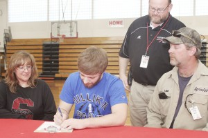 Photo by Keith Stewart SOV middle linebacker Walker Byers (center) signs his letter of intent to play football at Millikin University as his mother Melanie (left) and father, Luke (right) in addition to former head football coach Charles Brown (standing) watch during the April 9 ceremony at Sullivan High School.