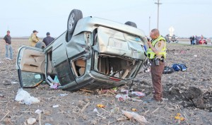 Photo by RR Best Moultrie County Deputy Sheriff Aaron Thomas calls in the license plate of a 2002 Mazda van after it flipped three times after exiting route 32 between Sullivan and Lovington Saturday evening. Two occupants were ejected from the vehicle. Both were life flighted to Carle Foundation Hospital in Urbana.