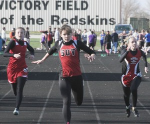 Photo by Keith Stewart Emily Neuhauser lunges forward as she takes first in the 100m dash. (Left) Arthur-Lovington/Atwood-Hammond's Abby Foreman finishes in fourth.