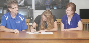 Photo by Keith Stewart Sullivan High School alumna Maggie Plank (center) signs her letter of intention to compete in volleyball at Omaha, Nebraska's Grace University Friday May 30 as her father, Jim (left), and mother Lori (right) watch approvingly.