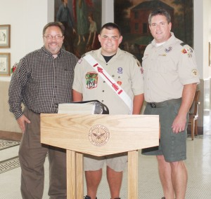 Submitted Pictured is former Troop 39 scoutmaster Gerry Wood (left), recently promoted Eagle Scout Benjamin Berner (middle), and current scoutmaster Jeff White at the formal unveiling of Berner's Eagle Scout project, a list of more than 2,000 Moultrie County veterans and current armed forces and a podium upon which the list will sit.