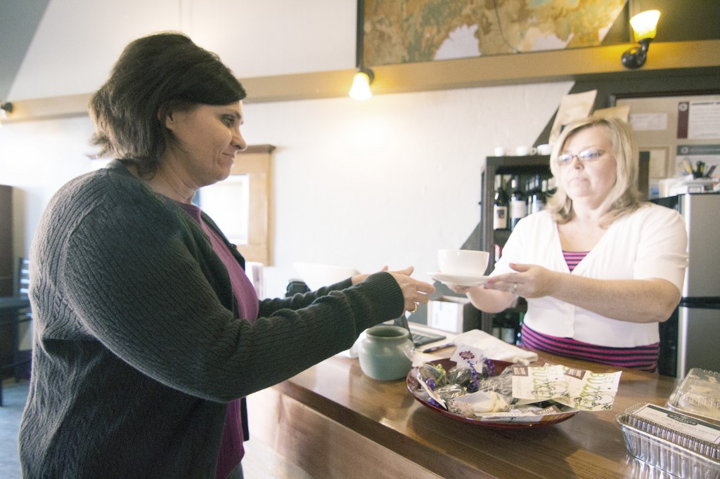 Photo by Keith Stewart Terrie Golden (left) receives her latte from owner Cathrine Craig Tuesday afternoon at 5 West coffee and wine lounge.