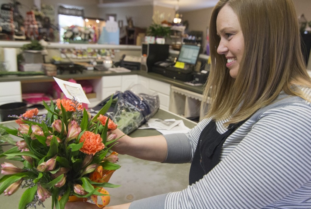 Photo by Keith Stewart Lesa McDaniel puts the finishing touches on a flower arrangement Monday morning. McDaniel, along with her mother Kimberlie Elkins, are the new owner/operators of the Flower Pot in Sullivan.