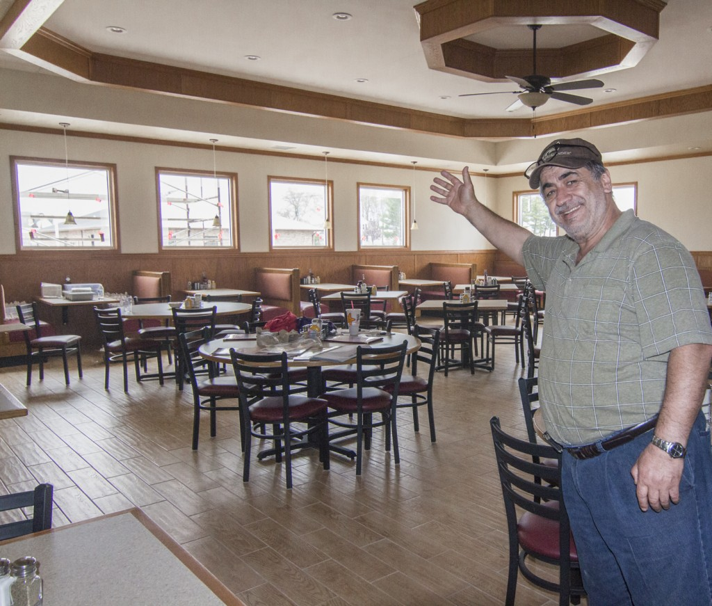 Photo by RR Best Red Apple Family Restaurant owner and operator Steve Sadikoska shows off his new dining room Friday afternoon. Sadikoska and his family reopened the restaurant Monday after it burned down last July.