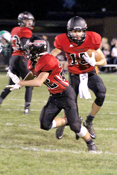 Photo by RR Best  Alec Ballinger (15) turns the corner getting protection from Drew Hubbard (22) as he racks up yardage on a great running night for the Redskins in their victory over the Meridian Hawks.
