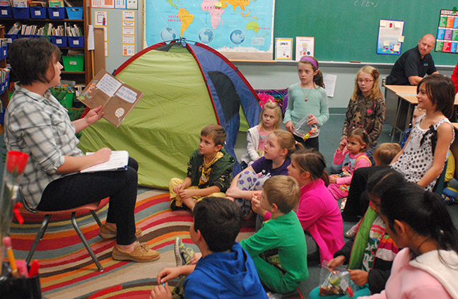 "Photo by Mike Brothers Librarian Leah Fleming reads Pigeon Needs a Bath to ""campers"" during Family Reading Night at Sullivan Elementary School November 19. The Secretary of State Family Reading Night Camping theme was complete with tent and stories around the campfire."