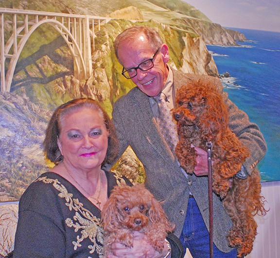 Photo Mike Brothers Arthur gallery owners Joan and Jerry Winters pose in front of a mural of their former home in Carmel, Calif.  along with store pets Monet and Manet.