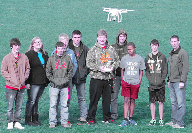 Photos by Mike Brothers With the Drone in the foreground the class learns how to maneuver. Pictured from left: Eric Mercer, Olivia Buxton, Conner Sheehan, Ethan Macklin, Kam Roley, Kyle Burford, T.J. Williams, Jackson Masters, Wesley Wise, ag instructor.
