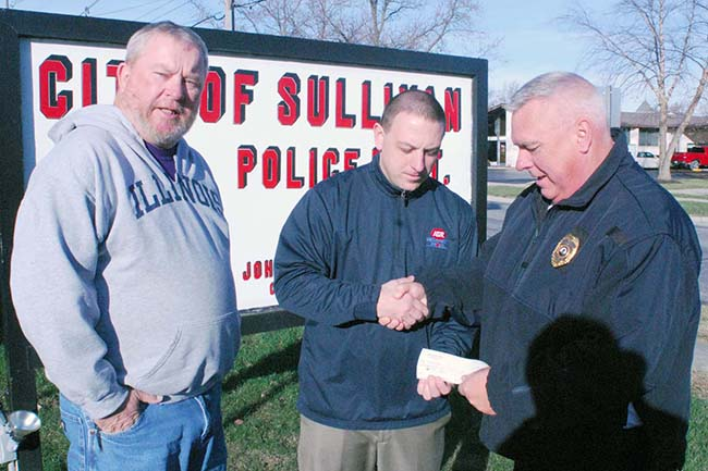 Photo by Mike Brothers Sullivan IGA donated $500 to Secret Santa. IGA manager Pat Stinson  (center) presents check to Secret Santa representatives Police Chief John Love (right) and Greg Foster.