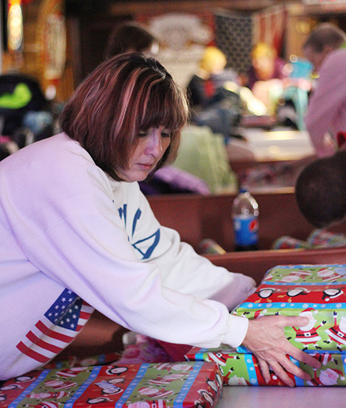 Photo by Darian Hays Lovington's charitable non-profit Sparrows completed their annual gift giving program over the weekend. A dozen people gathered at the East End Tavern in downtown Lovington to wrap gifts for 120 children and 11 challenged adults.  The annual Christmas auction was held Dec. 5 with the funds raised used for the toy and clothing shopping for the 120 people on the Sparrow shop list. In addition to wrapped gifts which were delivered Sunday, Lovington residents were also allowed to choose from extra clothing and toys which were on display at the Lovington Ambulance Service Saturday.  Pictured is Sparrow volunteer Marsha Renfro putting final touches on wrapped gifts.