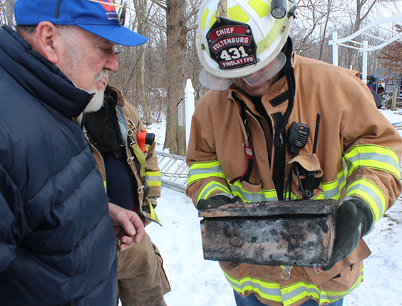 Photo by RR Best Fire Destroys Rural Sullivan Home Findlay fire chief Ed Voltenburg presents burned strong box to Jim Binion following a blaze that totally destroyed his home on 850 E County Road outside Sullivan. Windsor, Bethany and Sullivan fire departments joined to fight the 12:16 p.m. January 20 fire. Sullivan Fire Department reports indicated the Binions saw flames in the center of the house and were able to escape to their daughter's home next door. They watched the family home destroyed by fire while sitting at son-in-law and Findlay fire chief Voltenburg's home. Red Cross also lent assistance at the fire scene. Firefighters remained at the Binion home using a backhoe to help expose hot spots until 4 p.m.
