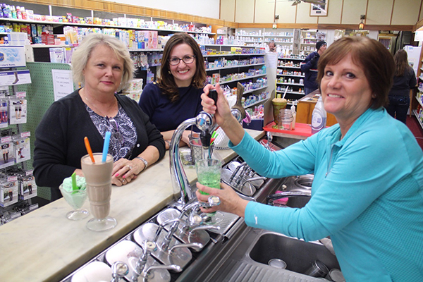Photo by RR Best Old fashioned soda fountain drinks and sundaes are among the attractions that remain at Dicks Pharmacy. From left: regular customer Patti Grant and Dicks Pharmacy owner Cindi Reed prepare to enjoy a hand dipped shake and green river from server Cheryl Grove.