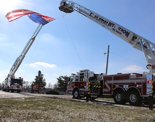 Photo by Mike B rothers Bethany Fire District Leads Procession  Sullivan, Lovington, Mt. Zion and area first responders joined family and friends to honor the passing of Jerry L. Clark, Chief Engineer of the Bethany Fire District. Following the 11 a.m. January 12 services at McMullin-Young Funeral Home in Sullivan the Bethany Fire District led Clark's procession to Marrowbone Cemetery in Bethany where Sullivan and Mt Zion Fire District ladder trucks displayed the American Flag at the entry. Bethany American Legion Post #507 performed military rites. Serving the fire district for more than two decades, Clark was also a member of the Okaw Fire Association and Bethany American Legion Post.