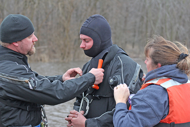 Photo by RR Best Moultrie County dive team members Jesse Scribner, Rob Martz and Amanda Farley secure equipment before diving down to hook the submerged car from the drink.