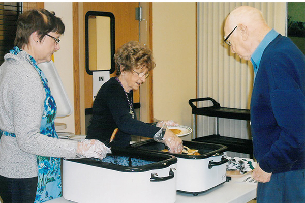 Photo furnished A Shrove Tuesday meal is being served 4:30-6 p.m. Fat Tuesday, Feb. 9 at First United Methodist Church in Sullivan. Elaine Daniels (left) and Fern Patton served Norm Buckner a plate of pancakes and sausage during the first Shrove Tuesday meal in 2015.