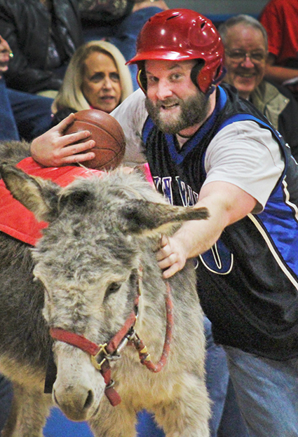 Photo By Sonya Best Sean Kirksey deals with the classic problem during the Okaw Valley FFA donkey basketball challenge in Findlay Saturday, March 19. How to get back in the saddle with a basketball in your hand. Thrills and spills filled the evening with the students falling to the more experienced administration team. View more photos here.