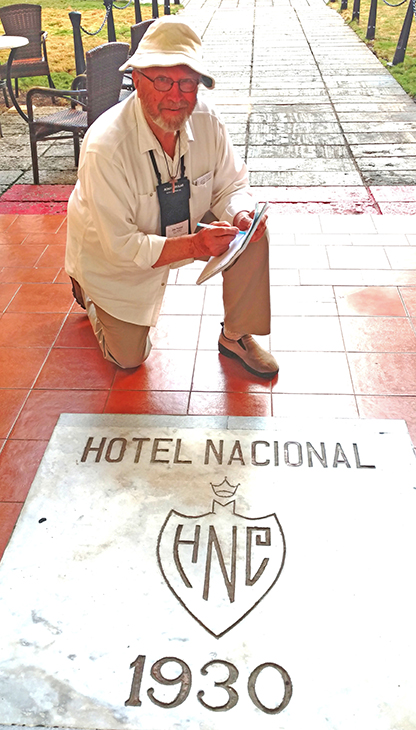 Sullivan's Joe Pound kneels at entrance of Hotel Nacional in Cuba