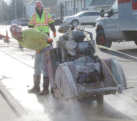 Photo by Mike Brothers Penhall Company started early Monday sawing away the old sidewalk in preparation for removal. Traffic was rerouted and the noise level on the square increased as the city project includes new accessible walks and resurfacing the street around the square.