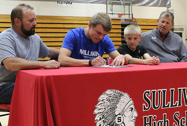 Photo by Mike Brothers Ballinger is Millikin Bound SHS athlete Alec Ballinger signed a letter of intent to play football for the  Millikin University Big Blue with teammates and students attending. Pictured from left: father Ed Ballinger, Alec, brother Aiden Ballinger and Sullivan High School head football coach Gerald Temples.