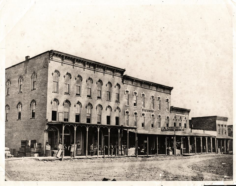 "Pictured above is the north side of square in Sullivan in1881. The far left 3-story building is theTitus Opera House. The second floor corner office is John R. Eden Law Office. The first floor corner is a general store. Standing in front of the stairs to the Opera room and next to his new sewing machine is G.O. Andrews, a tailor. Next is L.M. Spitler and his son. Occupying the Vadakin ""Drugs"" building was Mose Ansbacher, men's clothing. Where TNT is today was occupied by the ""Journal"" newspaper. Harry J. Pike, Jeweler occupied one of the small wooden buildings, and Dr. Lewis was located in the end building. Photo taken by A.S. Creech and is oldest known photo of that side of square. Please submit photos to the News Progress for future consideration. Originals will be saved for return or forwarded to Moultrie County Historical Society. If you have any other information, please contact the Moultrie County Historical Society at 217-728- 4085."