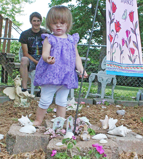 Photo by Bernie Sanders Fairy Garden Sullivan gardener Tia Punches spent the week creating a Fairy Garden, sprinkled with shells collected from various beaches over the country. Above Tia's great-granddaughter Harlequinn inspects shells from the garden while grandson Sebastian looks on.