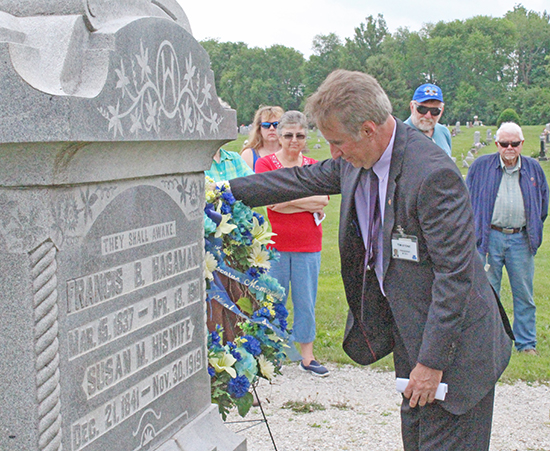 Photo by Mike Brothers DMH CEO and President Tim Stone places a wreath on Sue Hagaman's grave.
