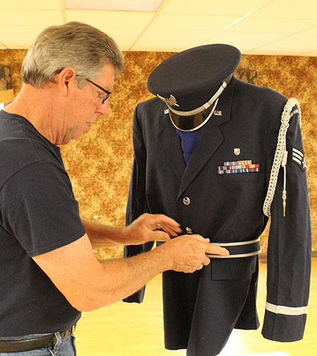 Photo by Mike Brothers Terry Muzzy prepares Honor Guard uniform that is part of the military memorabilia display at Bethany Celebration this weekend.