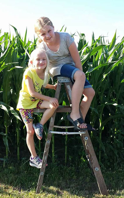Photo furnished July Corn Cailyn, 9, and sister Cara,6, checked out the height of corn near Sullivan recently and found out it was a lot more than knee high in July. Cailyn and Cara are daughters of Eric and Candace Elder (SHS class of 1990) Murphy. Grandparents are Elvin and Leatitia Elder of Sullivan.