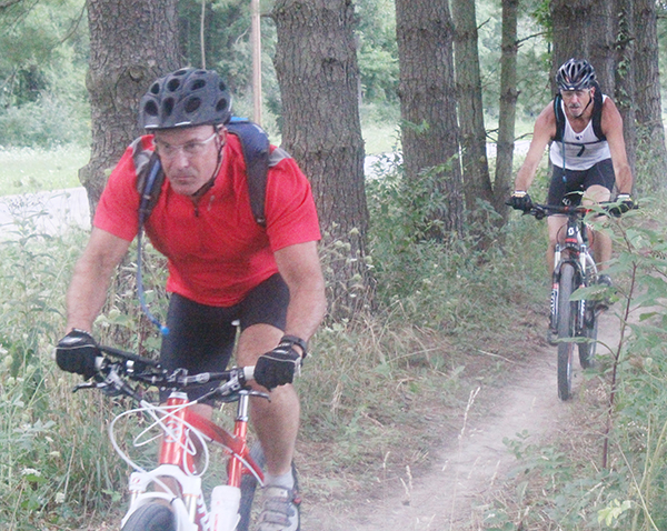 Photo by Mike Brothers CIMBA members Todd Harris (front) and Doug Lee of Sullivan ride a new section of the Camp Camfield trail in preparation for the Aug. 14 Clash at the Camp.