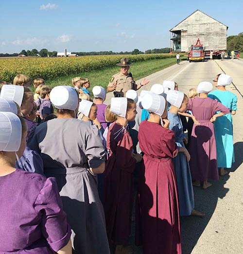 Photo furnished Illinois District 10 Trooper explains safety issues to Mennonite school children observing the move of the first Amish home in the state to the future Amish Heritage Center location last week.