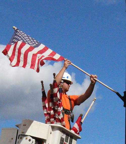 Photo by Mike Brothers Flags Wave Sullivan utility workers put the crowning touches on the city's Labor Day weekend placing flags around town Friday in preparation for the last holiday of summer.