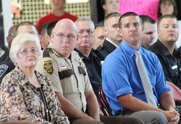 Photo by Mike Brothers Patriots Day reflections were depicted in a video watched by the assembly at Sullivan High School. Above Sullivan Mayor Ann Short, Sheriff Chris Sims, Chief of Sullivan Police John Love and guest speaker Nathan Becker watched somber memories from 9-11-01.