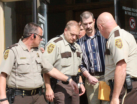 Photo by Mike Brothers Convicted of murder Michael Yost is escorted from Moultrie County Courthouse Sept. 15 by Sheriff Chris Sims (right) Chief Deputy Gary Carroll (left) and Deputy Gary Eller (second from left). Yost remains in Moultrie County Jail until his sentencing October 21.