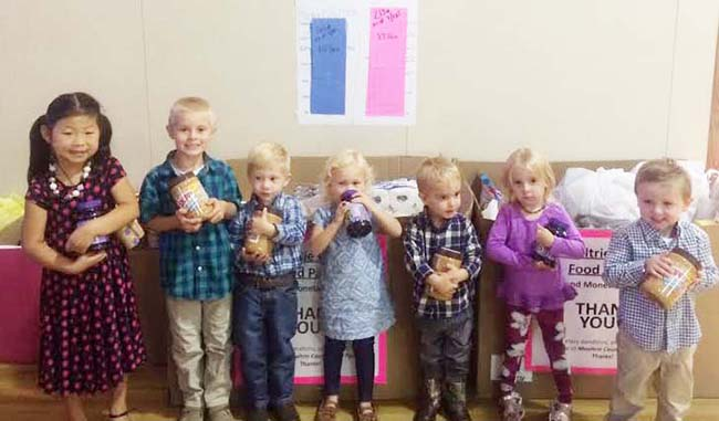 "Photo courtesy Heather Clements UMC Kids Spread Cheer to Food Pantry Pictured are children from the Sullivan First United Methodist Church with jars of peanut butter and jelly that were collected over this last month for the local food pantry. From left to right: Adalee Foster, Vance Young, Leo Lane, Livie Lane, Henry Kuhns, Scarlett Perrott and Judd Sanner. Church members and children were challenged to fill several large boxes to supply the food needs for the month of September for the food pantry. The children were also in a contest to collect a total of 300 pounds of peanut butter and jelly (150 lb. of peanut butter for boys, 150 lb. jelly for girls). The kids surpassed their goal by collecting 164 lb. of peanut butter and 213 lb. of jelly in hopes of ""Spreading the Word"" to the community of Sullivan and helping those in the community."