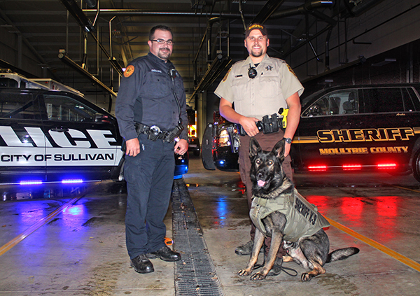 Photo by RR Best Archie Has Got a New Vest Sullivan patrolman Adam Collins and Moultrie County sheriff's deputy Kaleb Smith, K-9 patrol Archie's handler, is pictured with Archie in his new bullet and puncture proof vest. Sullivan police dept.'s annual Rushmore law enforcement golf outing generated the extra funds from the 50/50 raffle and hole sponsors to help purchase the new vest. Golf outing coordinator Collins received approval from the sheriff's K-9 unit for the donation with which police were able to purchase the $1800 vest for $1100.