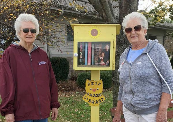 Photo By Ellen Ferrera Lending Library at Mason Point Judith Brown (l) and Jean Dulik visit the little lending library at Mason Point. Ellen Dick-Ferrera, former librarian, with some help from friends at the Senior Center established the free lending library at Mason Point earlier this year. Visitors can rest on the bench and read books from the box or borrow them to bring back later. Located along a popular walking route, people living in the duplexes can take a book or leave a book, with eveyone sharing from the little library.  Ferrera hopes to eventually include books from the main library and share magazines as well.