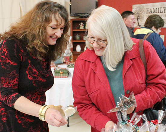 Flesors' Candies at Cathrine's Devon Flesor of Flesor's Candy Kitchen helps Verna Tice select gifts at the annual benefit sale for the Moultrie County Food Pantry held at Cathrine's Gallery in Sullivan.