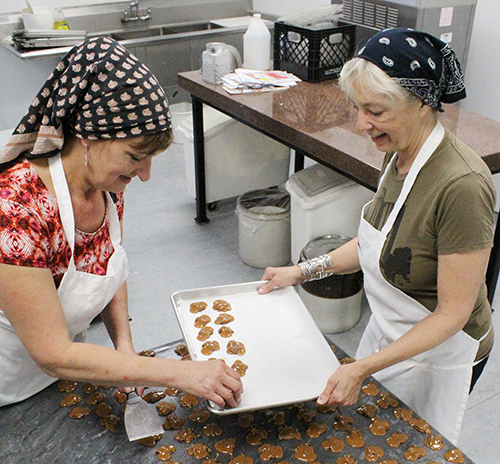 """Photo by Mike Brothers Flesor Candy Kitchen owners (from left) Devon and Ann place Paul's Pecan Favorites before packaging. The """"turtle style treat"""" has been a Candy Kitchen favorite since Grandfather Gus created it back in 1901."""