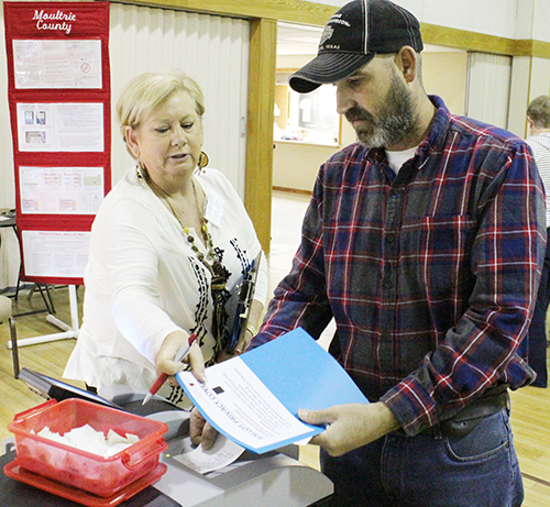 Photo by Mike Brothers Election Day Sullivan Precinct #6 voters were in the polling place at First United Methodist Church Nov. 8. Above Kurt Thompson prepares to place his ballot in the voting tabulator with some instruction from election judge Angie Coy.