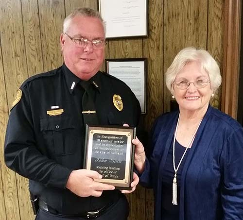 Photo furnished Chief John Love accepts appreciation plaque from Mayor Ann Short at a recent city council meeting. Chief Love begins retirement November 23 after serving the city of Sullivan for 28 years.