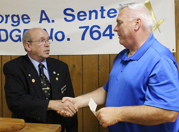 Photo by Mike Brothers Sullivan Masons Donate Following the annual Grand Masters Banquet at the George Sentel Masonic Lodge in Sullivan recently, the lodge made donations to the Secret Santa program and the Moultrie County Food Pantry.  Above, Senior Warden Mike Rollins presents Sullivan chief of police John Love with a $500 check for the Secret Santa program in Sullivan and Bethany. The same amount was donated to the Food Pantry. The Masonic Lodge's annual golf outing in August generates funds allowing the George Sentel lodge to support the scholastic bowl and academic bowl for all schools as well as scholarship presentations to Sullivan, Okaw Valley and Windsor high school students and a variety of other community programs.