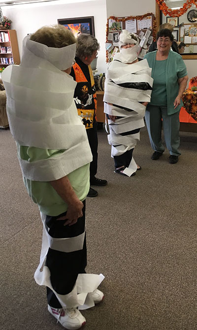 Photo by Ellen Ferrera Mummy wrap was popular during the Halloween party as two teams competed against time to wrap their partners into a mummy with rolls of toilet paper.